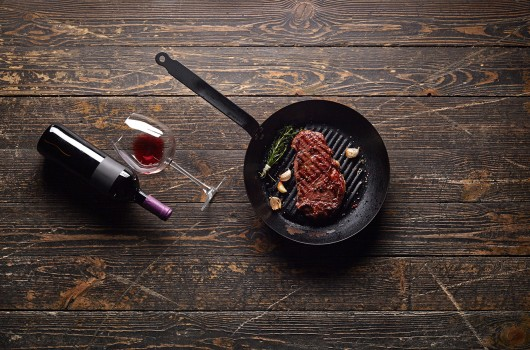 Marbled beef steak in a grill pan with a bottle of wine and wine